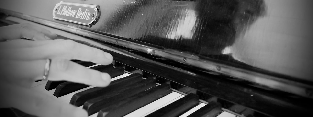 An artistically grainy, black and white photo of the skillful             hands of a musician, hovering above a piano keyboard, just about to engage in playing a moving piece